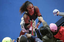 Serena Williams signs autographs after winning her Women's singles semi-final match against Croatia's Mirjana Lucic-Baroni.