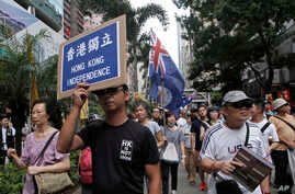 Protesters hold placards and wave Hong Kong colonial flags during the annual pro-democracy protest in Hong Kong. As the Asian financial center prepares for legislative elections in September, a new wave of radical political activists are planning to