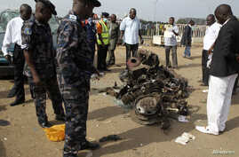 Air Commodore Charles Otegbade (3rd L), director of search and rescue operations, looks at the wreckage after a bomb blast at Nyayan bus terminal in Abuja, April 14, 2014.