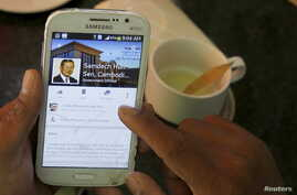 A person uses a smartphone to look at the Facebook page of Cambodia's Prime Minister Hun Sen, during breakfast at a restaurant in central Phnom Penh, Cambodia October 7, 2015. Cambodia's Prime Minister Hun Sen is taking a belated leap into the digita