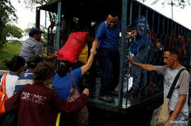 A woman is helped to get on a cargo truck used as public transportation in Valencia, Venezuela, July 11, 2018.