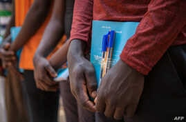 FILE - Newly released child soldiers receive school supplies as part of a re-integration kit which includes clothing and mosquito nets during a release ceremony for child soldiers in Yambio, South Sudan, on Feb. 7, 2018.