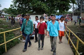 Men walk across a bridge inside the sports club where Central American migrants traveling with the annual Stations of the Cross caravan have been camped out, in Matias Romero, Oaxaca State, Mexico, April 4, 2018.