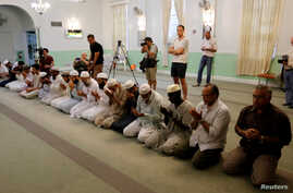 Worshippers listen as Imam Syed Shafeeq Rahman of the Islamic Center of Fort Pierce offers a prayer for victims of the Orlando shooting, in Fort Pierce, Florida, June 12, 2016.