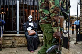 FILE - An armed police officer walks past an environmental protester wearing a skeleton costume as she demonstrates outside parliament against recent government plans to mine coal and open a coal-fired power plant, in downtown Nairobi, Kenya, June 5,