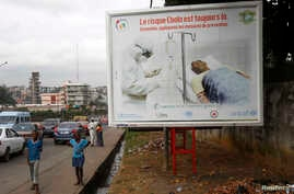 "People walk past a billboard displaying a government message about Ebola that reads: ""The risk of Ebola is still there. Let us apply the protective measures together"", in Abidjan, Ivory Coast, Sept.10, 2014."
