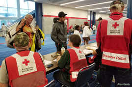 Evacuees arrive to seek shelter with Red Cross volunteers at the George Brown convention center after flood waters of Hurricane Harvey forced them to leave their homes in Houston, Texas,  Aug. 27, 2017.