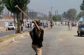 Indian paramilitary soldier aims his sling at Kashmiri protesters during during a clash between them in Srinagar, India, Aug. 9, 2013.