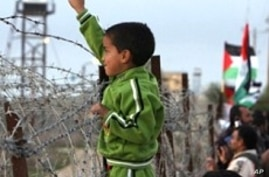 A Palestinian boy flashes 'V'  for victory sign during a protest near the Rafah border with Egypt, 31 Dec 2009, against the underground barrier Egypt is building along its border with the Gaza Strip