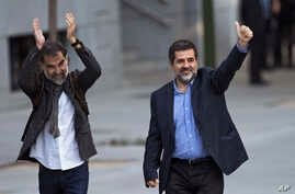 Jordi Cuixart, president of the Catalan Omnium Cultural organization, left, and Jordi Sanchez, president of the Catalan National Assembly, wave to supporters on arrival at the national court in Madrid, Spain, Oct. 16, 2017.