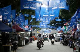 Flags from different political parties are hung along a street in Kuala Lumpur, Malaysia, Monday May 7, 2018.