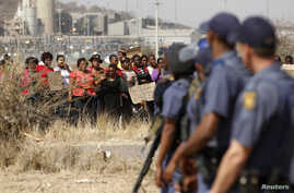 Police look on as women carry placards in protest against the killing of miners by the South African police on Thursday, outside a South African mine in Rustenburg, 100 kilometers northwest of Johannesburg, August 17, 2012.