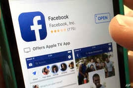 FILE - A user gets ready to launch Facebook on an iPhone, in North Andover, Mass., June 19, 2017. Facebook has made changes to fight false information, including de-emphasizing proven false stories in people's feeds so others are less likely to see t