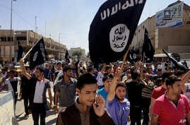 Demonstrators supporting the Islamic State of Iraq and the Levant (ISIL) carry al-Qaida flags in front of the provincial government headquarters in Mosul, Iraq, on June 16, 2014. ISIL fighters have released a recruiting video.