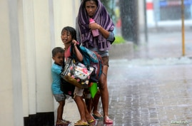 A mother takes refuge with her children as Typhoon Haiyan hits Cebu city, central Philippines, Nov. 8, 2013.