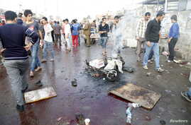 People gather at the site of suicide blasts in Baghdad's Sadr City, Feb. 28, 2016. The death toll from two suicide blasts in Baghdad's mainly Shi'ite district of Sadr City rose to 24 with more than 60 others wounded, police and medical sources said.