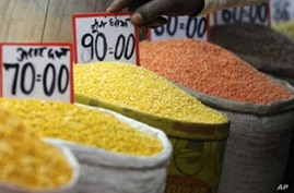 A shopkeeper arranges price tags on pulses at a wholesale market in the old quarter of New Delhi (File)