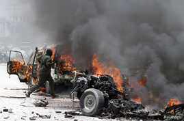 A police officer runs through burning vehicles at the scene of an explosion near the presidential palace in Mogadishu, Somalia, March 18, 2013.