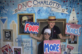Stephen Kimel and his wife Greta Kimel attract costumers to take pictures at their photo booth which was set-up at a street festival for convention goers ahead of the Democratic National Convention in Charlotte, North Carolina, September 3, 2012.