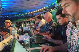 Rio Olympics A Brazilian Journey: In this Aug. 5, 2016 photo, Associated Press writers John Leicester, right, and Mauricio Savarese, second from right, work at the press table in the Maracana Stadium during the opening ceremony of the Summer Olympics