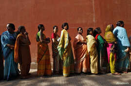 Women line up to cast their votes outside a polling station during the seventh phase of India's general election at Howrah district in the eastern Indian state of West Bengal, April 30, 2014. Around 815 million people have registered to vote in the w