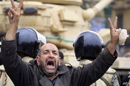 An Egyptian anti-Mubarak protester flashes the V sign in front of a tank in Tahrir square in Cairo, February 5, 2011