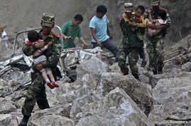 Soldiers carry children as locals follow them towards safer area after two earthquakes hit Zhaotong, Yunnan province, Sept. 7, 2012