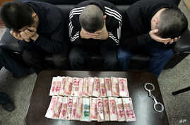 FILE - Suspects, hiding their faces, are held during a gambling raid in China.