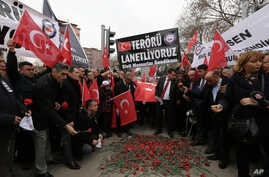 """Turkish civil servants hold a banner that reads """"We condemn terrorism"""" as they lay carnations at the site of Wednesday's explosion that killed 28 people in Ankara, Feb. 20, 2016."""