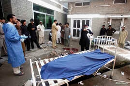 Relatives stand next to the body of a man in Lady Reading Hospital in Peshawar, March 21, 2013.