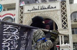 FILE - In this photo posted on the Twitter page of Syria's al-Qaida-linked Nusra Front on March 28, 2015, a fighter from Syria's al-Qaida-linked Nusra Front holds his group flag as he stands in front of the governor building in Idlib province, north