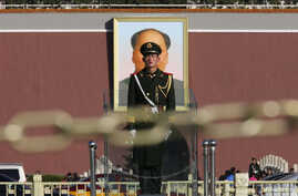 A Paramilitary soldier stands guard behind a chain as the giant portrait of the late Chinese Chairman Mao Zedong is seen in the background in Tiananmen square, Nov. 12, 2013.