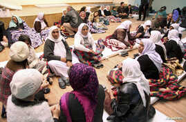 People from the minority Yazidi sect take refuge in a building in Shikhan, January 19, 2015.