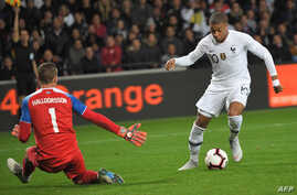 FILE - France's forward Kylian Mbappe (R) vies with Iceland's goalkeeper Hannes Thor Halldorsson during a friendly football match between France and Iceland at the Roudourou Stadium in Guingamp, western France, Oct. 11, 2018.