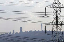 FILE -Electricity pylons cross the skyline of Johannesburg city, South Africa.