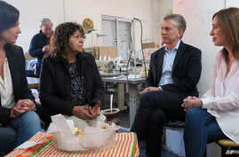 Argentina's President Mauricio Macri, Buenos Aires province governor Maria Eugenia Vidal, right, and Argentina's Minister of Social Development Carolina Stanley, left, talk to Lucila Godoy, president of the Osito Feliz textile factory, Sept. 18, 2017