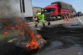 A fireman works to extinguish a burning tire barricade set on fire by protesting truckers, in Brasilia, Brazil, Nov. 9, 2015.