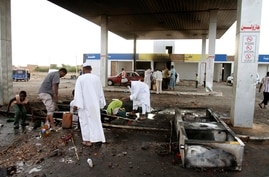 Men pick through debris after rioters torched a fuel station in Khartoum, Sudan, Sept. 26, 2013.