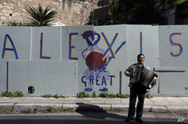 A busker plays music in front of a graffiti that refer to Greece's Prime Minister Alexis Tsipras in the traditional Plaka district of Athens,  Feb. 21, 2015.