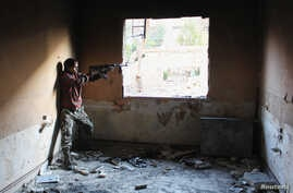 Mohammad, a 13 year-old fighter from the Free Syrian Army, aims his weapon as he takes cover inside a room in Aleppo's Bustan al-Basha district, Oct. 28, 2013.