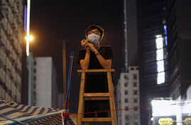 A student at a command post climbs on a ladder while watching for any aggressive moves by riot police at Mongkok shopping district in Hong Kong October 5, 2014.
