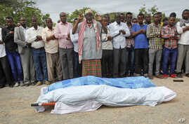 Mourners pray over the bodies of journalists Mohamed Abdikarim Moallim Adam, a reporter for the London-based Universal television, and Abdihakin Mohamed Omar, a producer for the Somali Broadcasting Corporation, at their funeral in Mogadishu, Somalia,