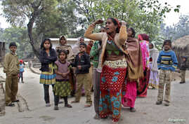 Family members mourn for their relatives, who died after consuming locally brewed liquor, outside their residence at Malihabad town in the northern Indian state of Uttar Pradesh January 13, 2015. At least 12 people died after drinking locally brewed