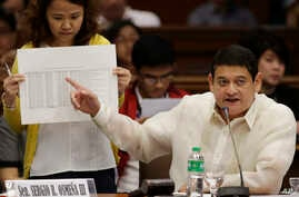 FILE - Philippine Sen. Teofisto Guingona III gestures as he shows a document during hearings into how about $81 million of Bangladesh's stolen funds were transmitted online to four private accounts at a branch of the Rizal Commercial Banking Corp. du...