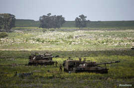 Israeli soldiers walks beside mobile artillery units near the city of Katzrin in the Golan Heights, March 19, 2014.