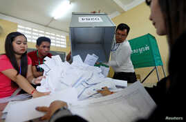 Officials begin the process of counting ballots after polls have closed in Cambodia's general election, at a polling station in Phnom Penh, July 29, 2018.