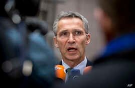 NATO Secretary General Jens Stoltenberg speaks with the media as he arrives for a meeting with European Union defense ministers at the EU Council building in Brussels, Nov. 18, 2014.