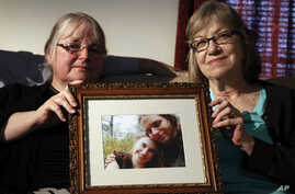 In this June 4, 2014, file photo, mother's Linda Boyle, left and Lyn Coleman hold photo of their married children, Joshua Boyle and Caitlan Coleman, who were kidnapped by the Taliban in