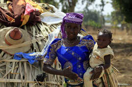 FILE - A United Nations report predicts a baby boom in Africa. Here, a woman carries her child in Nigeria's Kaduna State.