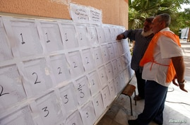 An official assists a voter to find his name before voting inside a school in Tripoli, June 25, 2014.